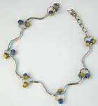 Wavy strip forming fashion bracelet with blue yellow color beads embedded