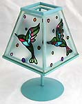 Blue table lamp style candle holder with painted bird figure on the cover